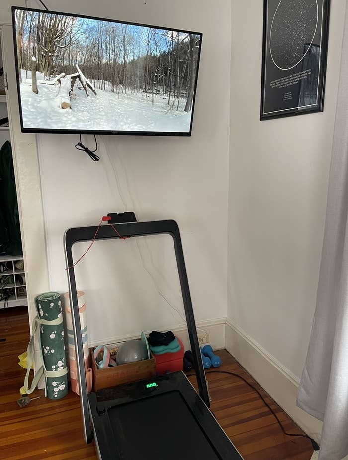 A treadmill with a TV above it