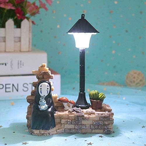 kaonashi figurine from spirited away next to a lamp post that lights up