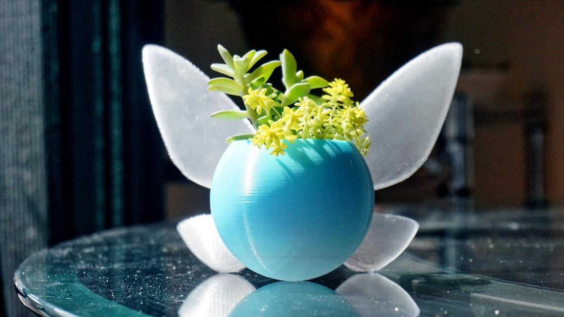 a round blue planter with fairy wings