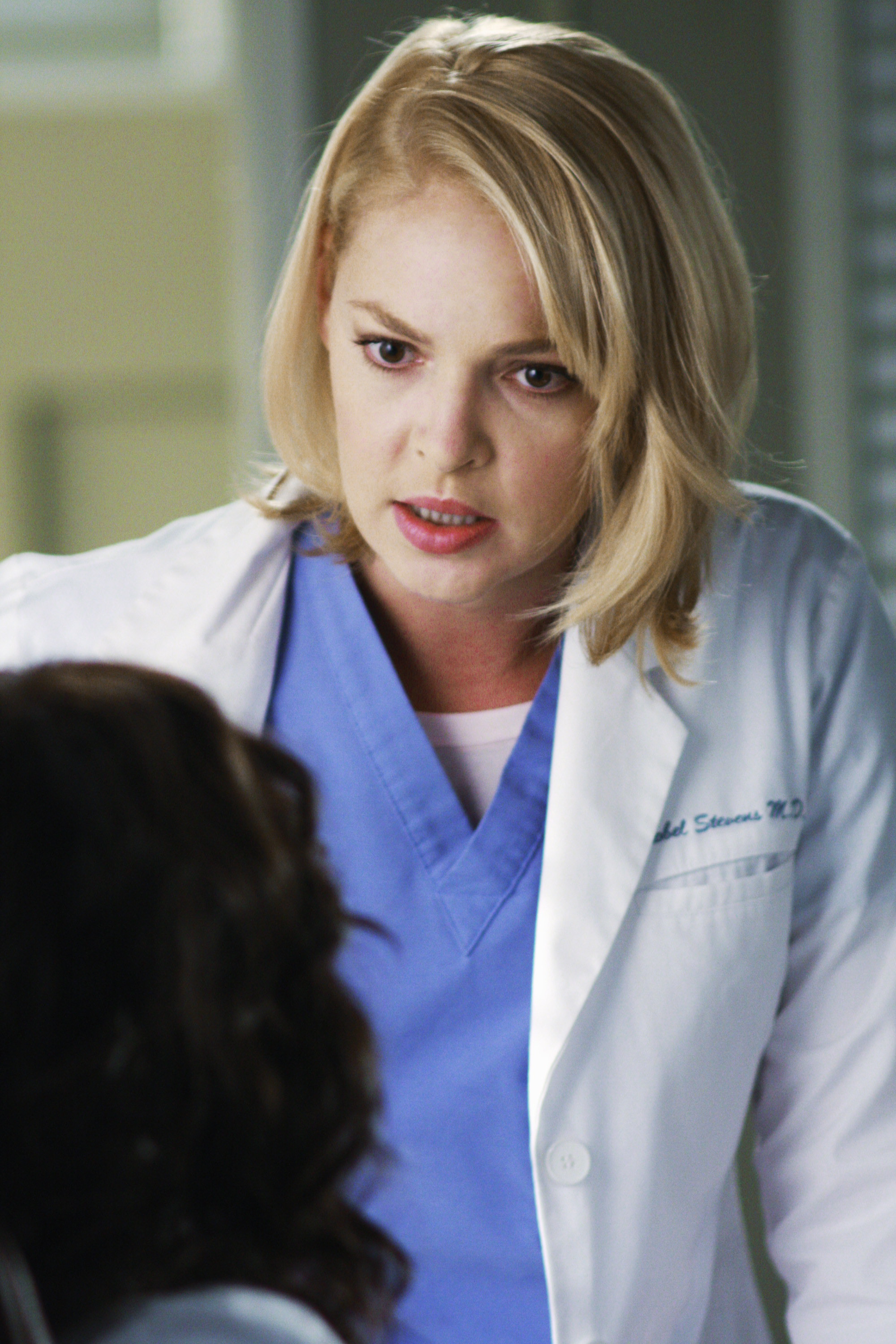Katherine Heigl, as Izzie Stevens, wears a white lab coat and blue scrubs while talking to a patient in Grey's Anatomy