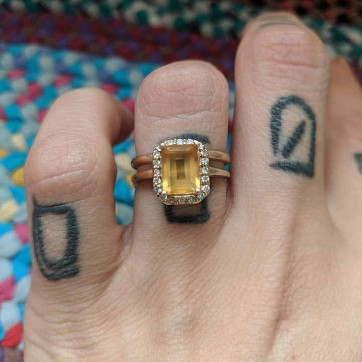 A reviewer photo of a ring with a cloudy yellow gemstone