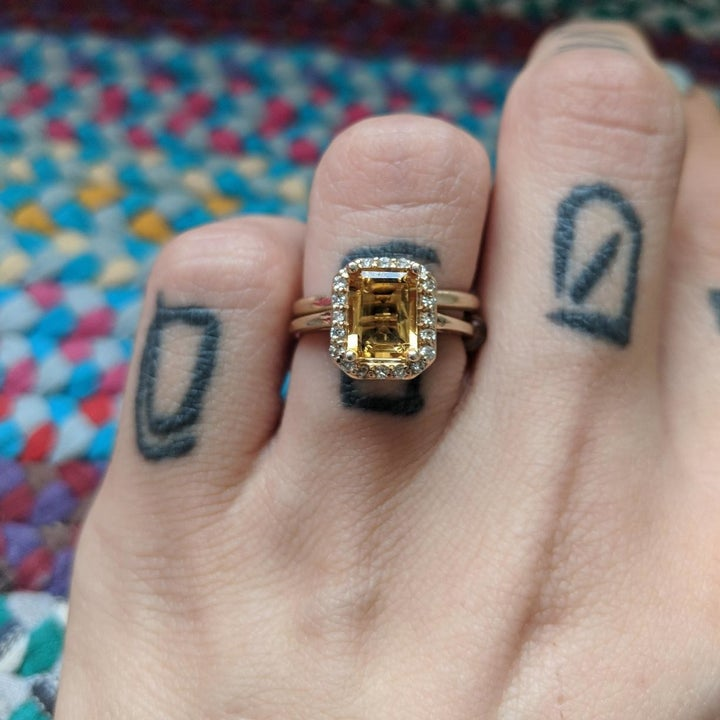 A reviewer photo of the same ring with the yellow stone shining