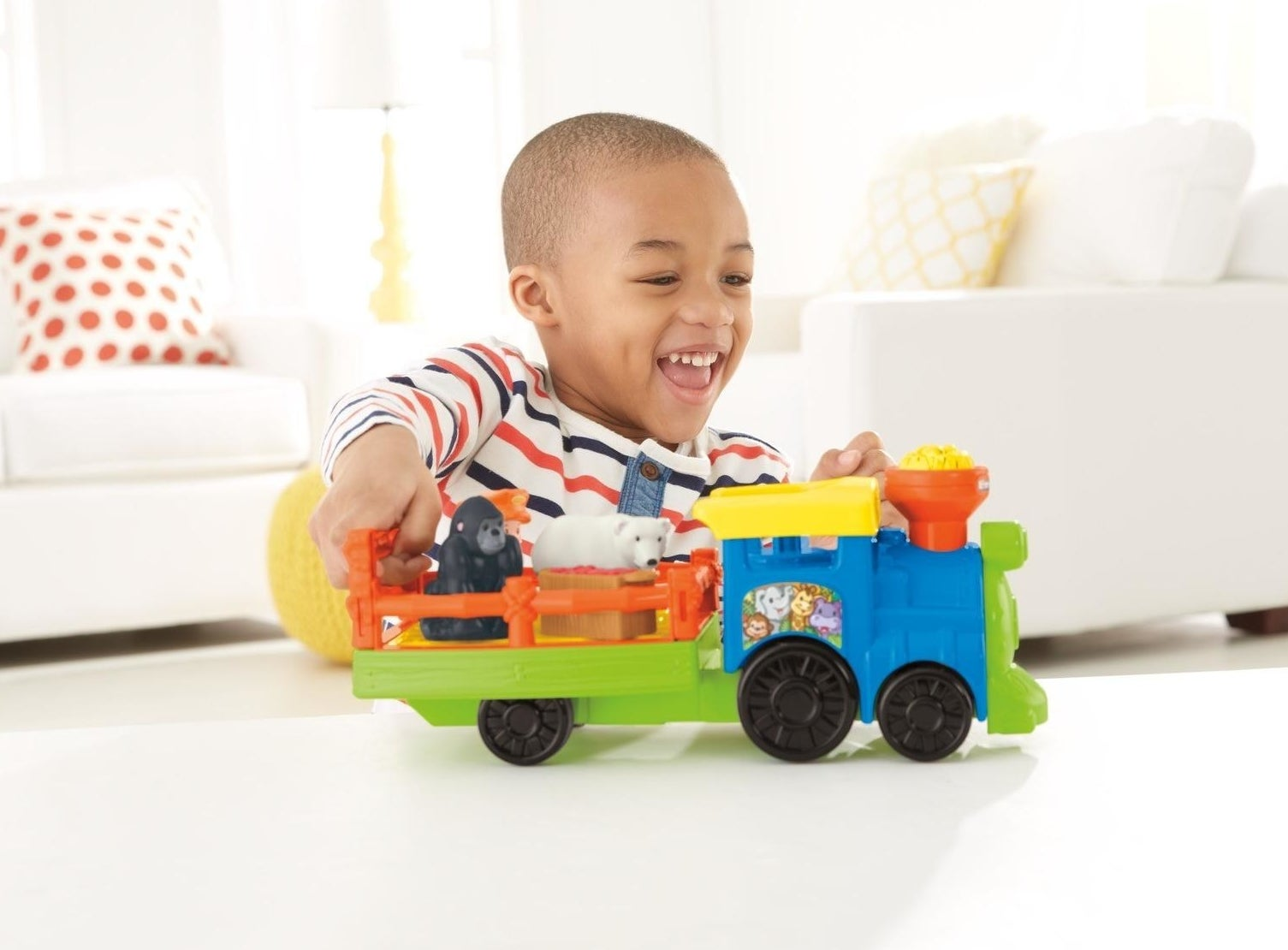 child playing with a toy train that has two animals in it