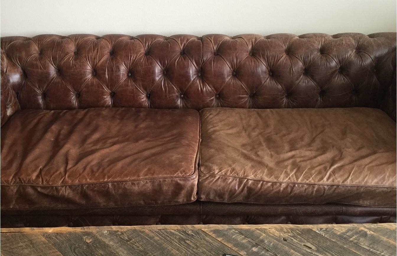 A reviewer brown leather couch with the left side looking darker and the right side appearing more faded