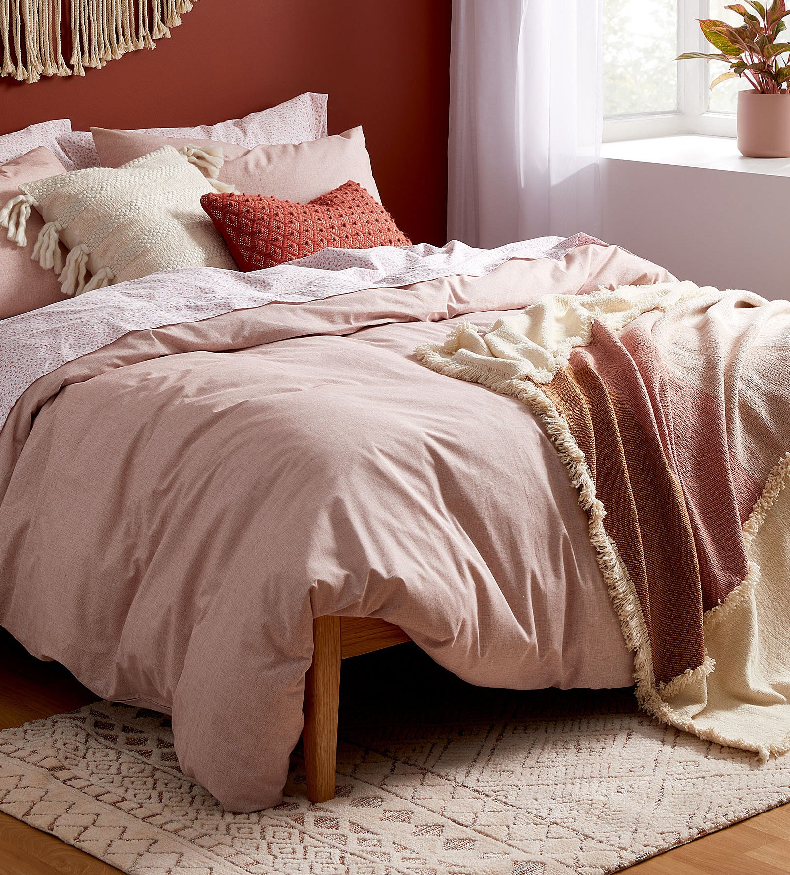 A comfy bed with bedding drooping over it stylishly