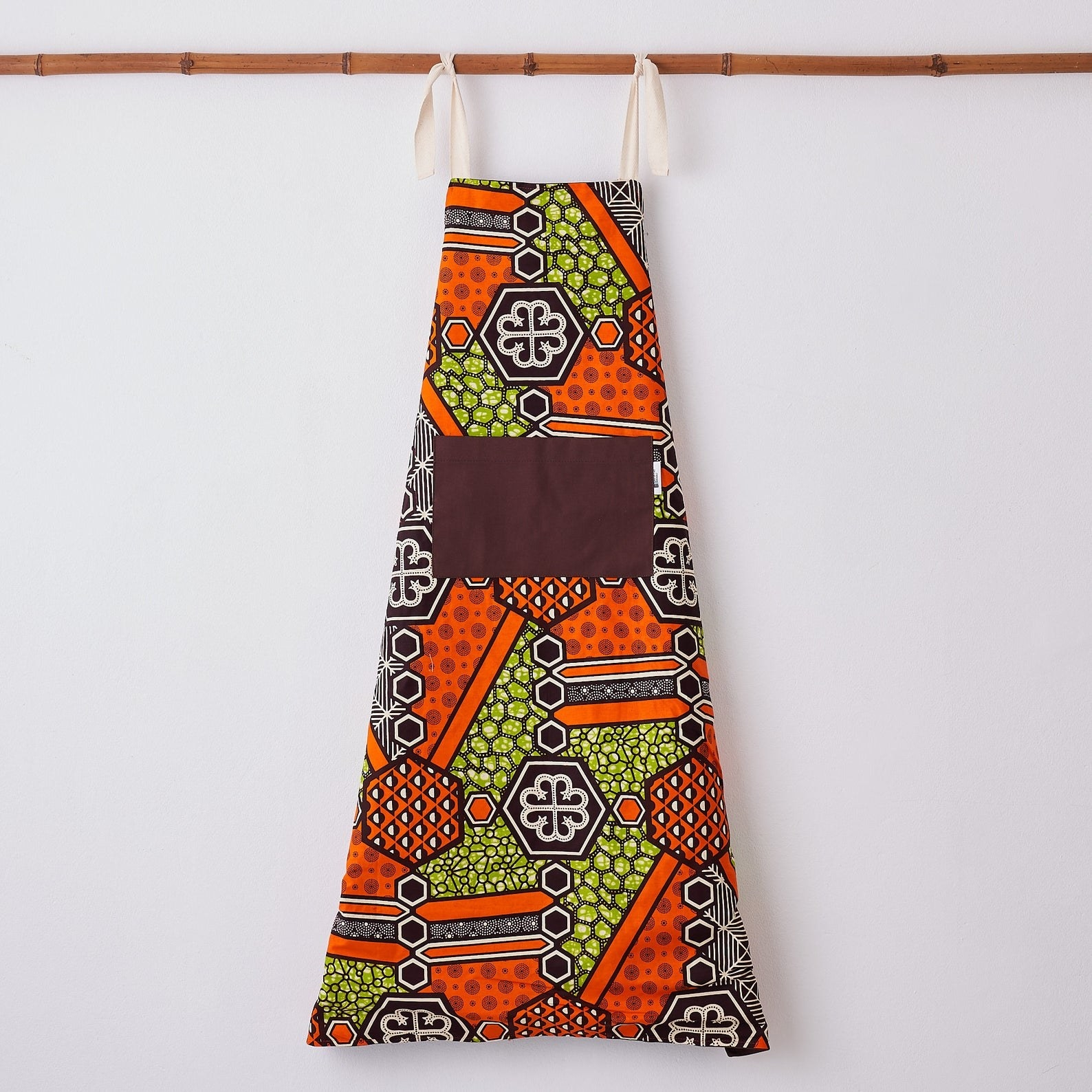 The graphic print apron in orange, purple, and yellow with purple front pocket and beige neck ties