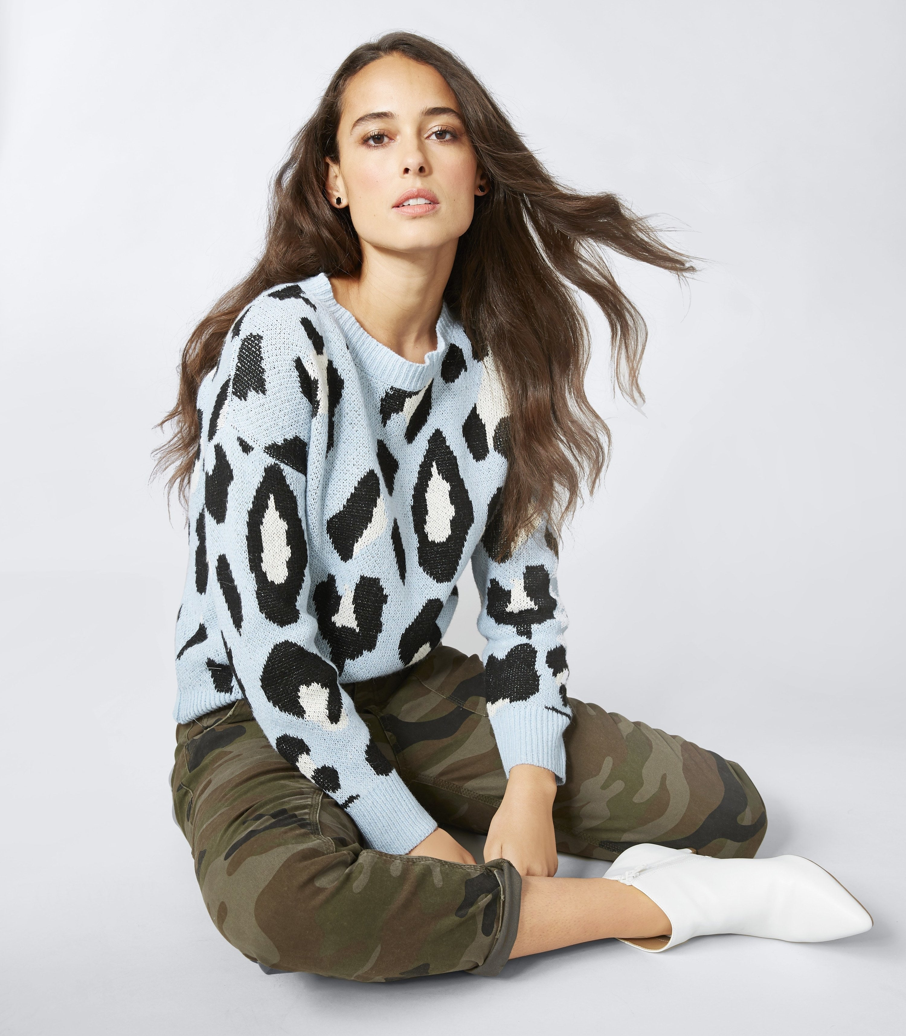 person wearing a blue leopard sweater and camo pants
