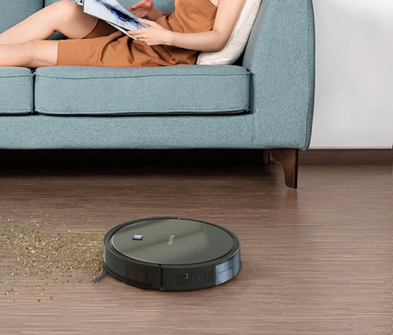 A robotic vacuum cleaning up a mess beside a person lounging on a couch
