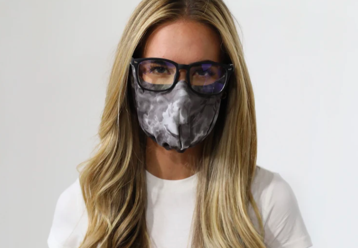 A person wearing their glasses and mask in black and white tie-dye