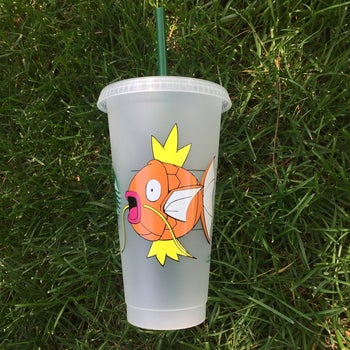 a starbucks cold tumbler cup with a magikarp on it