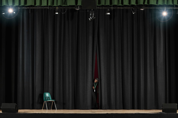 A student peeking through the curtains onto a high school auditorium's stage