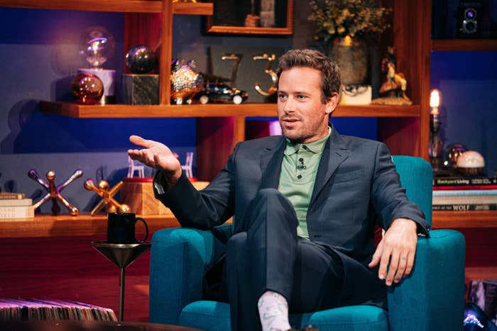 Hammer sits on a chair with his hand raised while wearing a dark blue suit and a green polo on The Late Late Show with James Corden