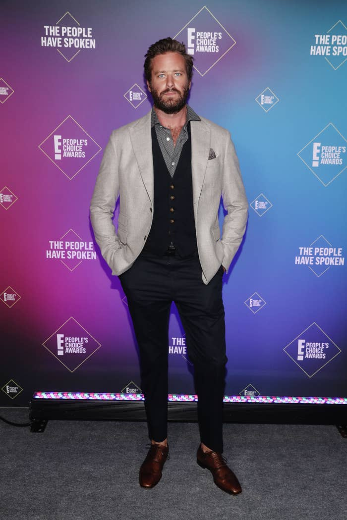 Armie Hammer wears a gray jacket, blue vest, grey patterned button-down, blue slacks, and brown shoes at the 2020 E! People's Choice Awards on November 15, 2020