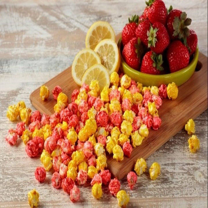 strawberry lemonade-flavored popcorn on a cutting board with strawberries and lemons