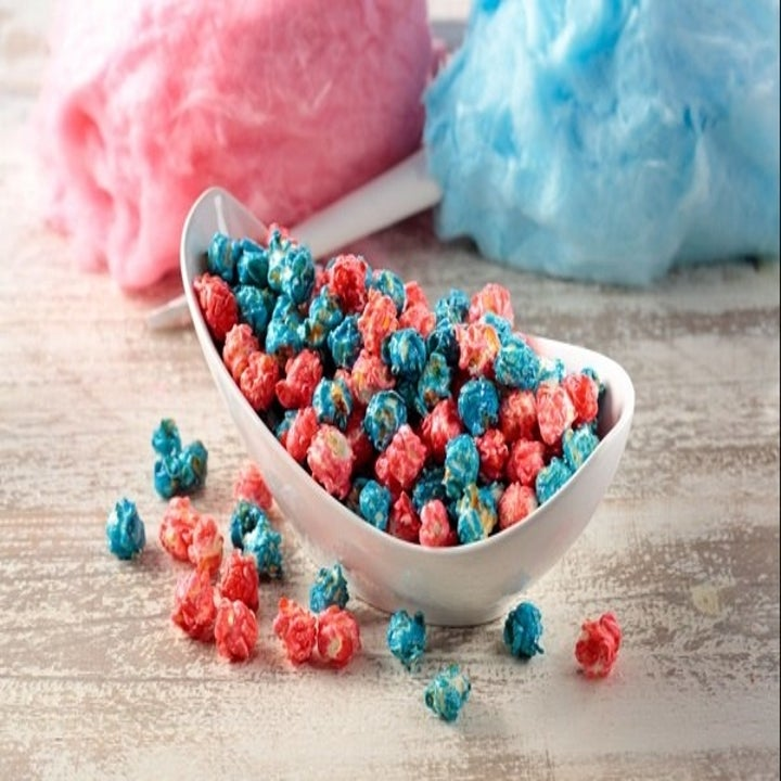 pink and blue cotton candy-flavored popcorn with cotton candy in the foreground