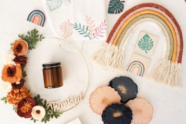 a rainbow made of yarn, a glass jar, and dried flowers