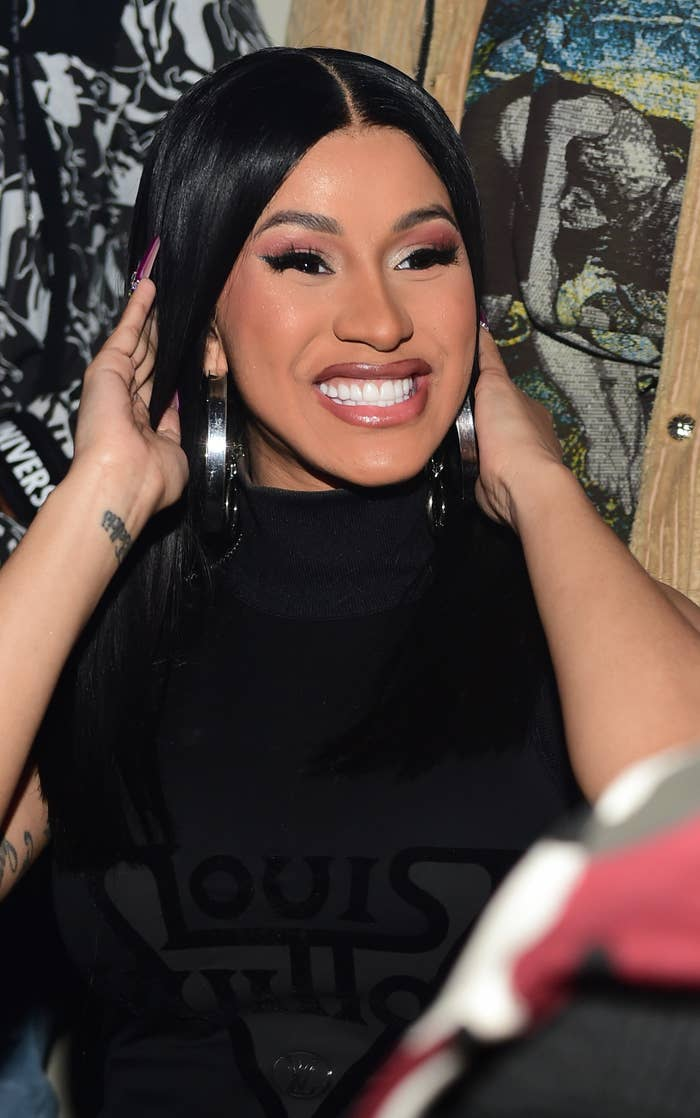 Cardi B, wearing a dress and sporting long straight hair and long nails, smiles at a party
