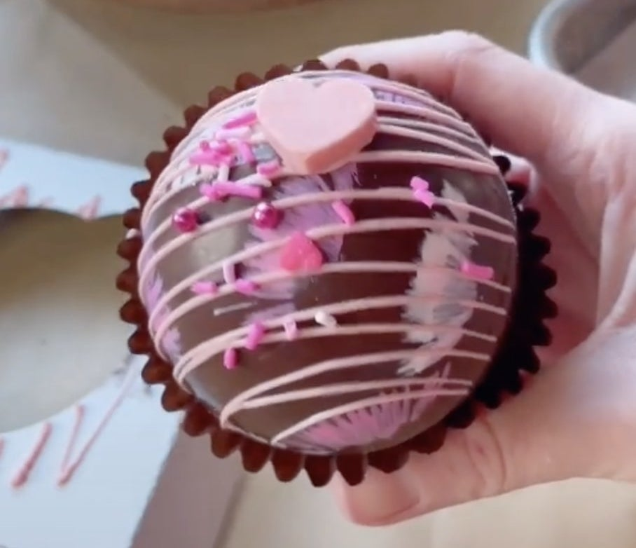 A chocolate sphere with sprinkles and pink chocolate drizzled on top