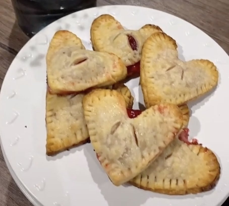 A plate of heart shaped pastries filled with red jam