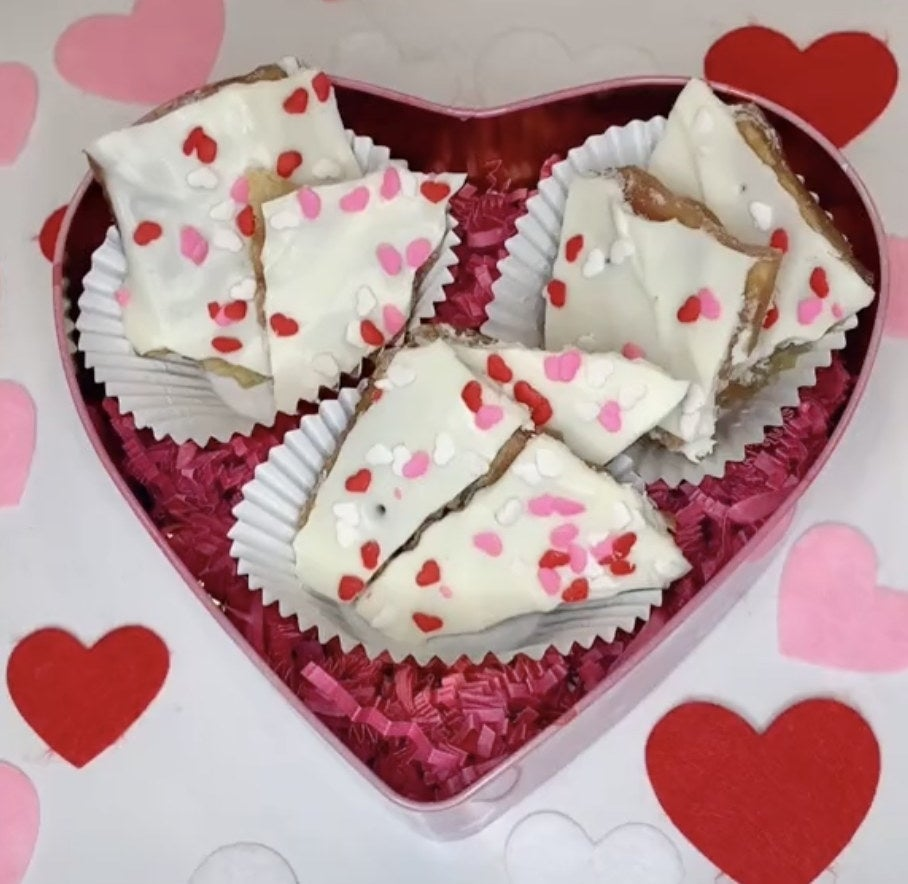 A tin filled with white chocolate pieces with pink heart spinkles