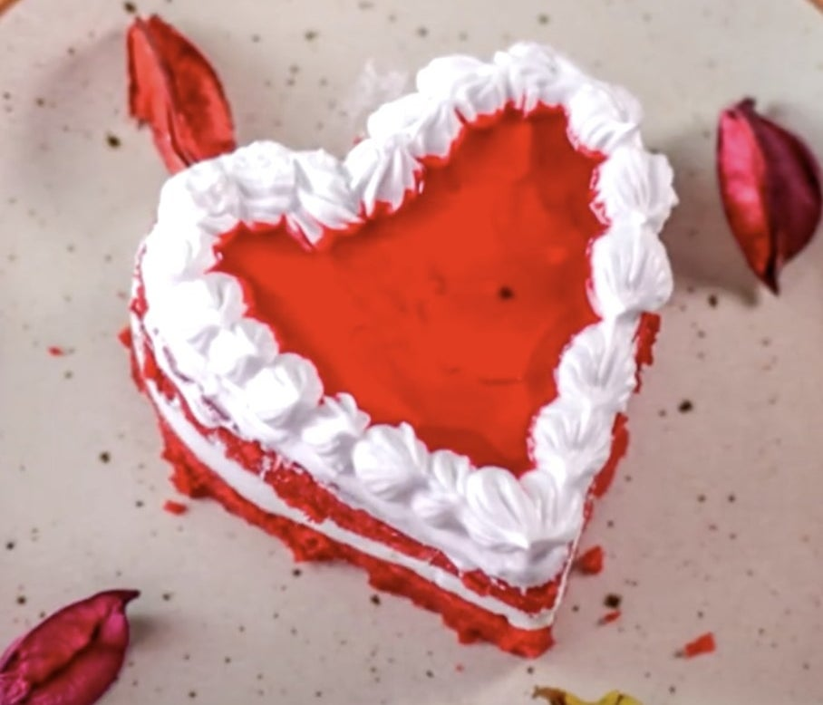 A red heart cake with white frosting in between layers