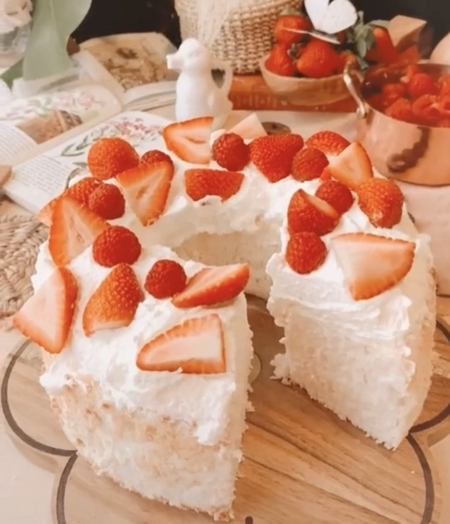 An angel food cake topped with strawberries with a slice cut out