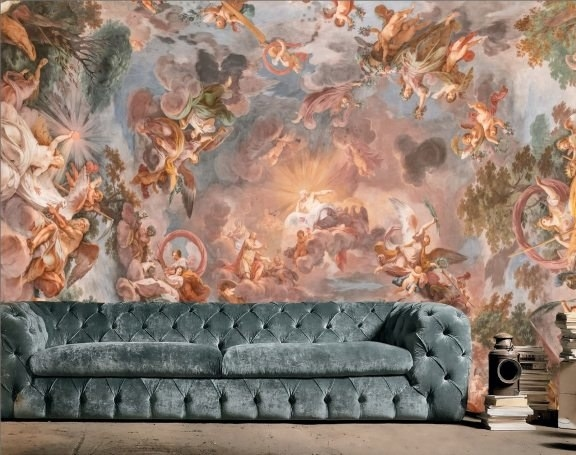 A green tufted couch and books sit in front of a Renaissance fresco wall mural