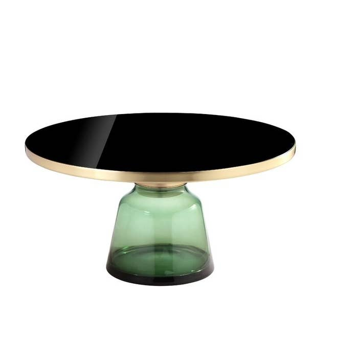 A pedestal coffee table with a brushed gold and glass top and a sculpted translucent base made of green glass