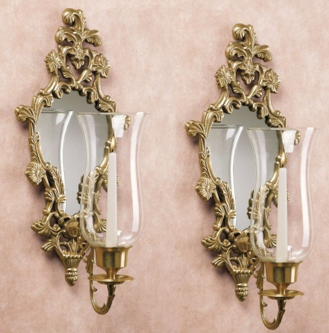 Two antique-gold ornate mirrored wall sconces holding glass tulip-shaped votives