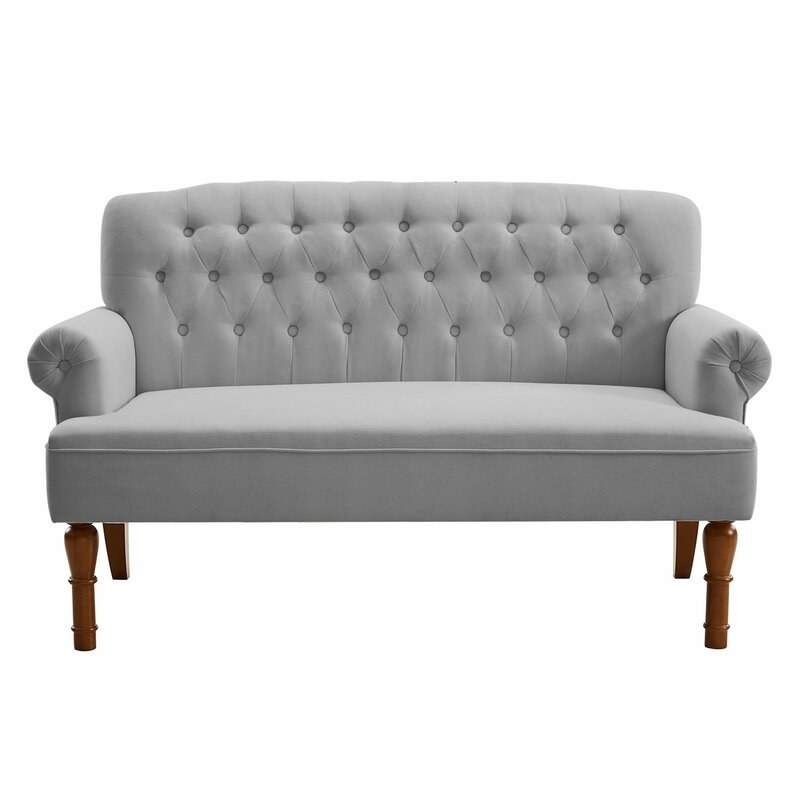 A light grey loveseat with tufted detailing and carved mahogany legs