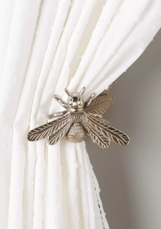 A pewter hook carved in the shape of a bee holding back a cotton curtain