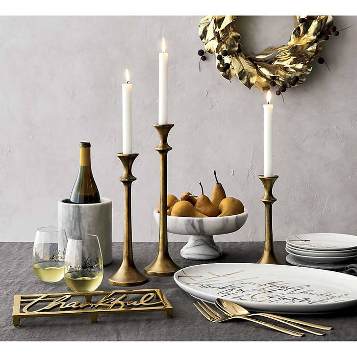 Brushed brass tapered candlesticks of varying height on a dressed table with marble and gold dish-ware