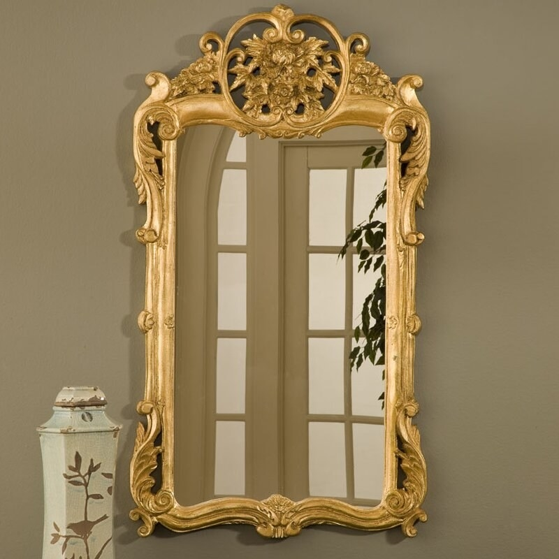 A carved white vase sits in front of an ornate gold mirror