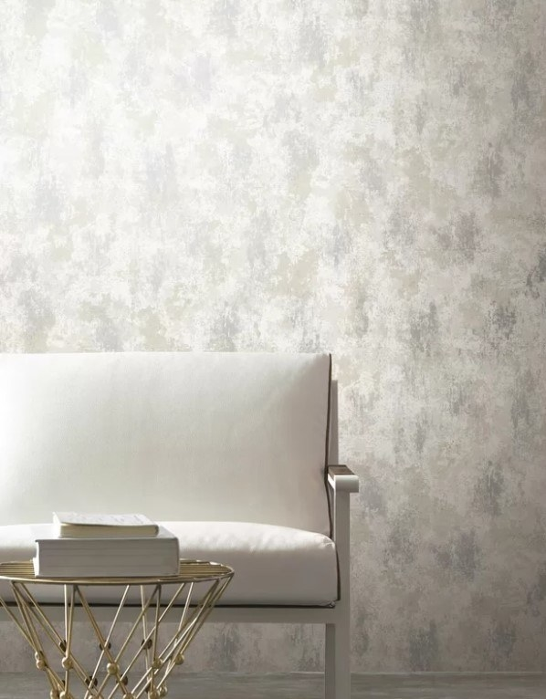 A white couch, gold wire table, and white books sit in front of shimmery metallic wallpaper.