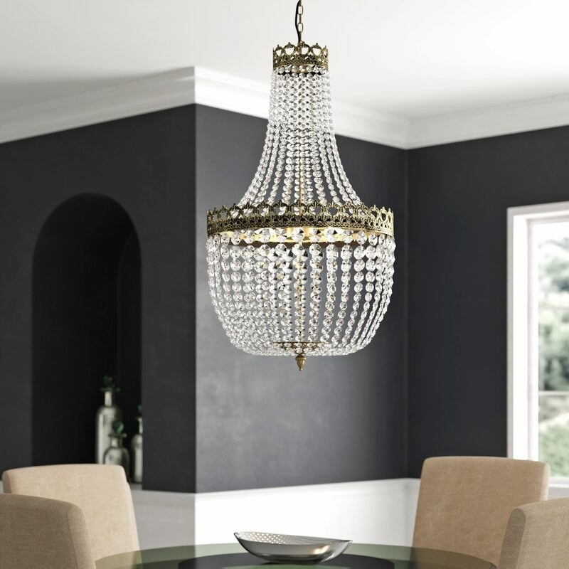 An empire-style gold and crystal chandelier hangs over a round glass table in a chic dining room