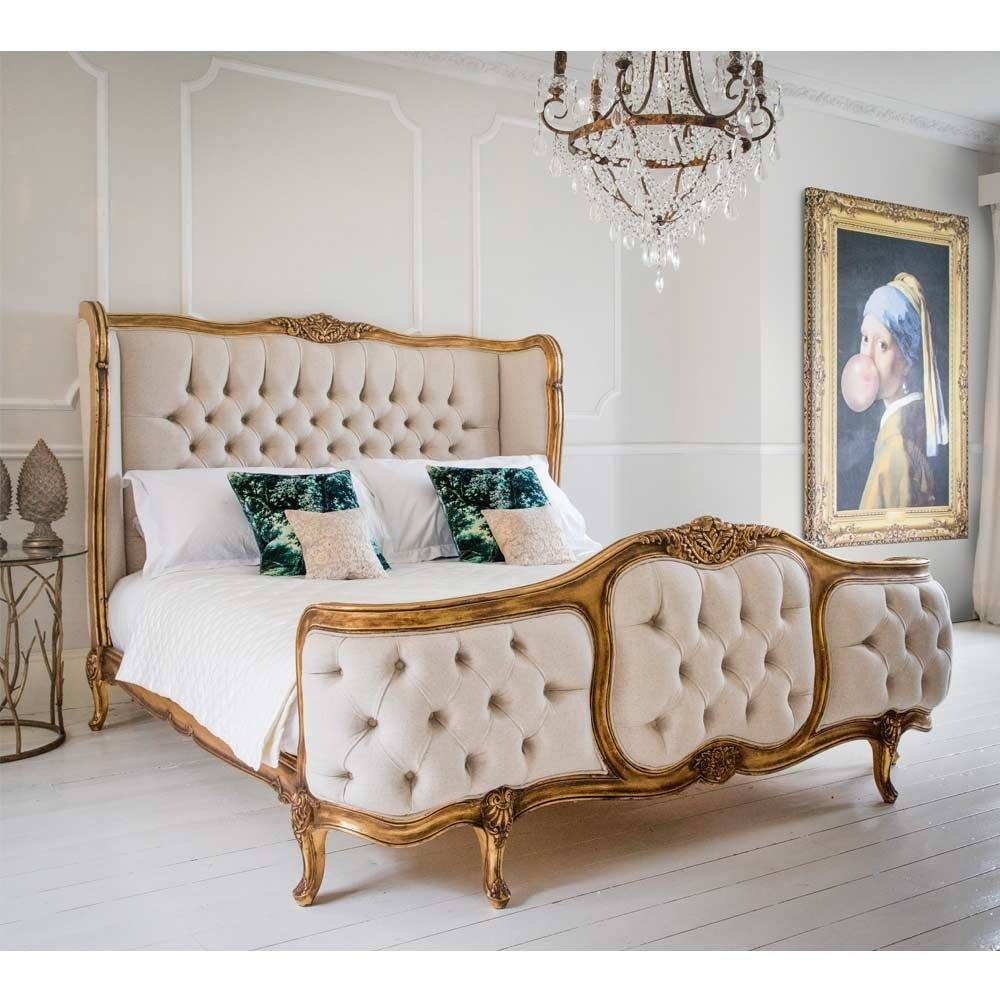 A room with a gold chandelier, a classic painting, and a gold wire side table features a large white tufted bed with ornately carved legs and frame made of gold-brushed mahogany