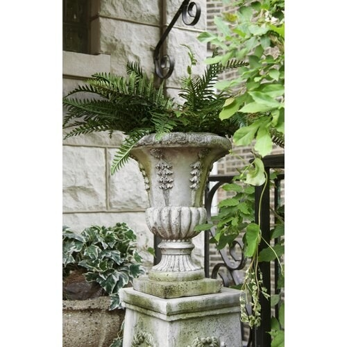 A plant-filled garden space features a stone urn with a fern planted inside it