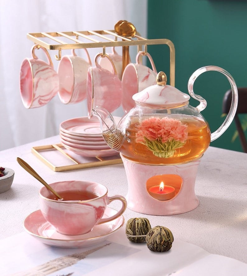A table features a marbled pink tea set with a glass teapot sitting on a matching warmer with a lit tea light candle underneath