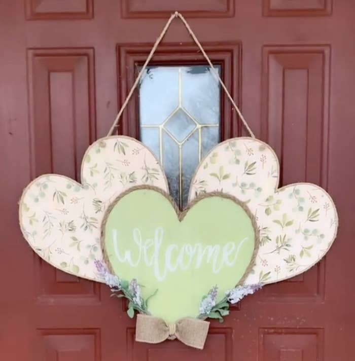 A door hanger with three hearts in a row filled with a pink floral pattern