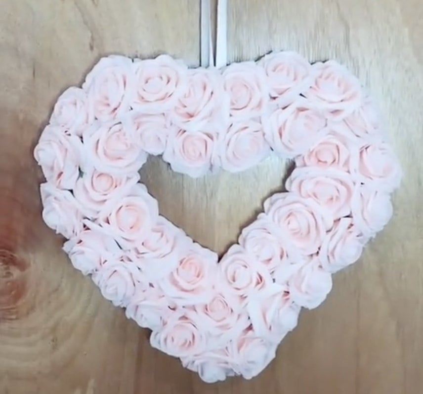 A heart shaped wreath filled with pink roses
