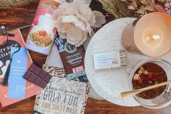 Books, herbal tea, chocolate bars, a candle, and dried flowers on a table top