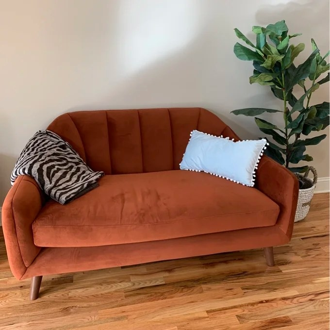 The loveseat with a pillow on top and a blanket draped over