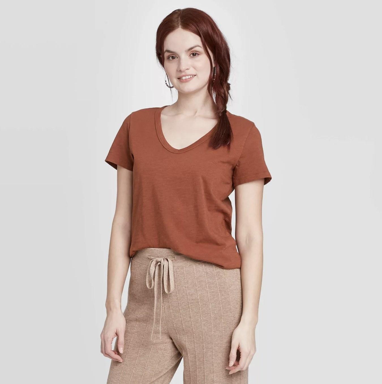 Model is wearing a burnt orange v-neck t-shirt