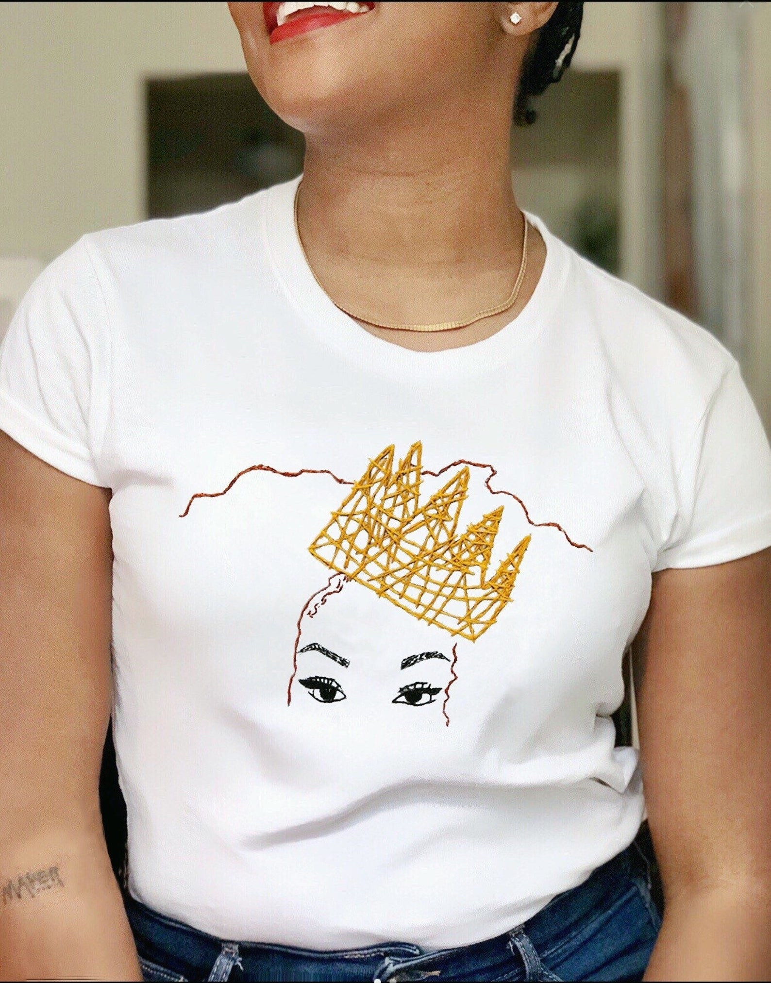 model wearing a t-shirt with a gold embroidered crown over a face just showing eyes and very fleeky eyebrows
