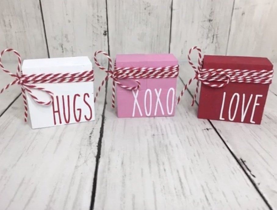 White, pink, and red blocks with hugs and love written on them