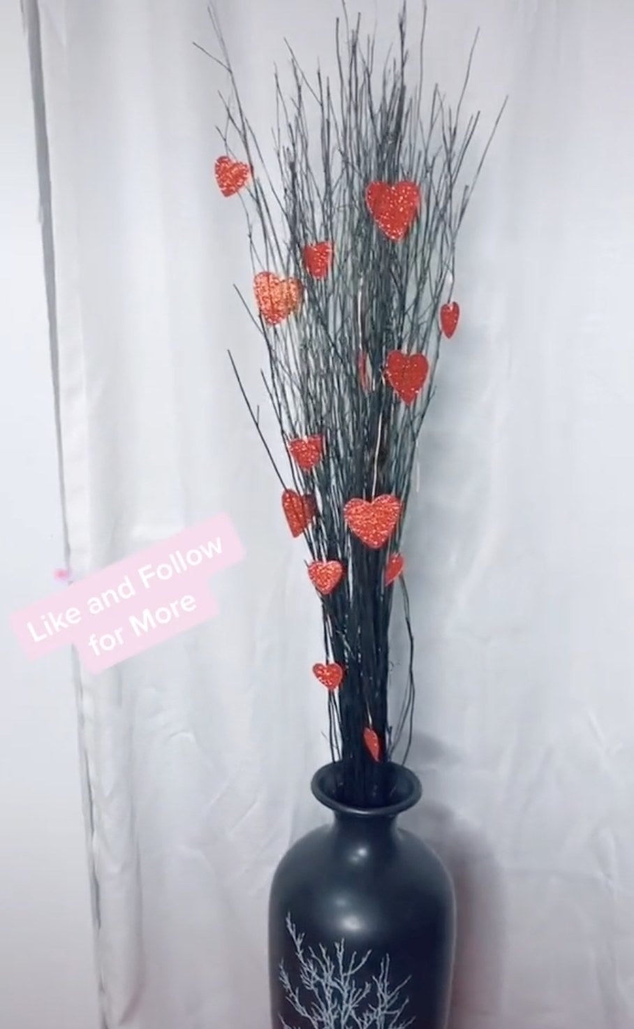 A black vase filled with decorative sticks and hearts