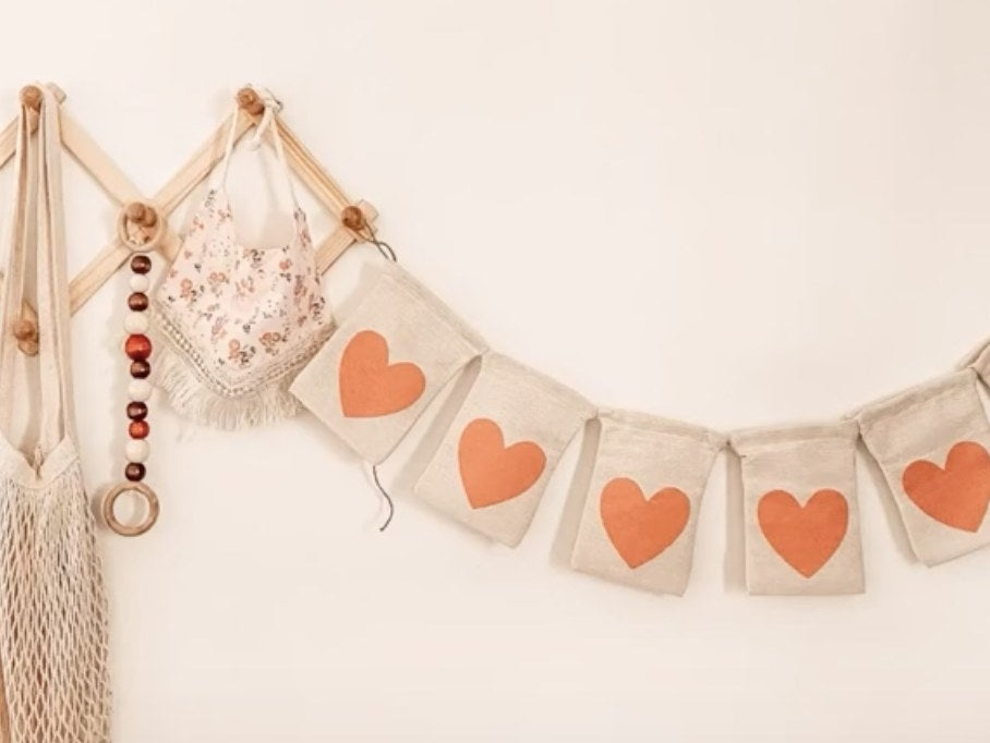 A banner made of pieces of burlap with red hearts on it