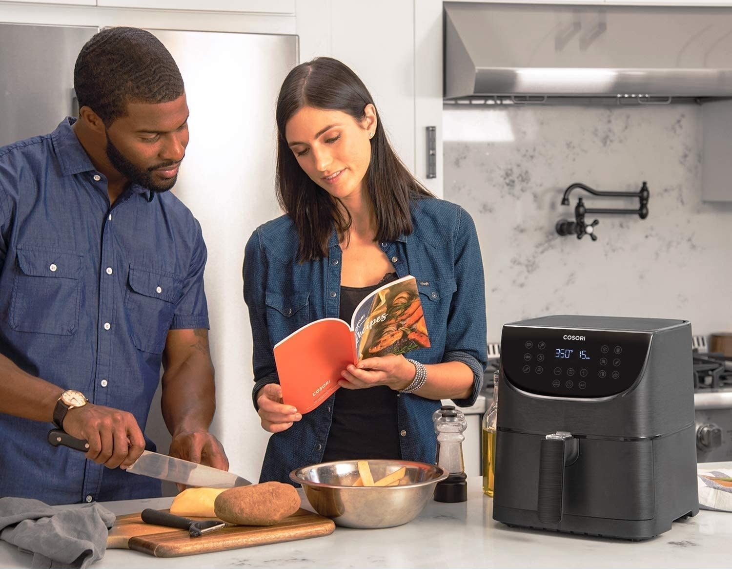 Two people cooking next to the air fryer