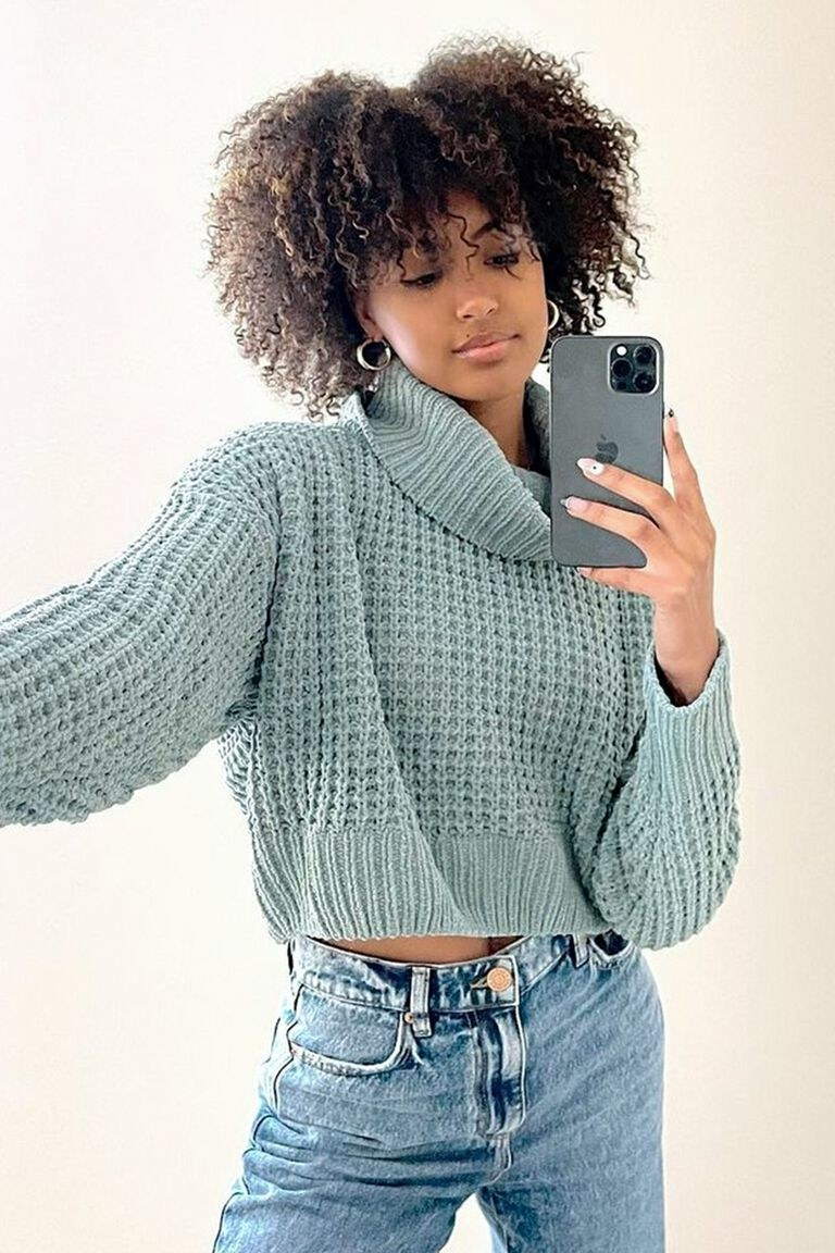 a model wearing the turtleneck sweater in green