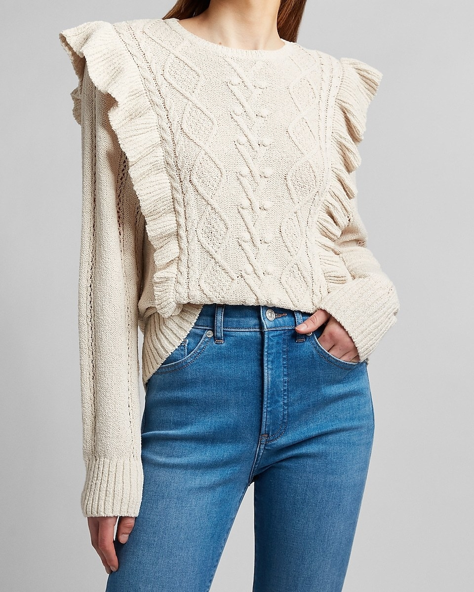 a model wearing the sweater in cream